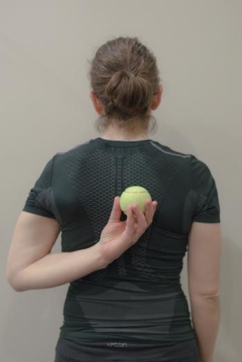 Hold tennis ball on upper back